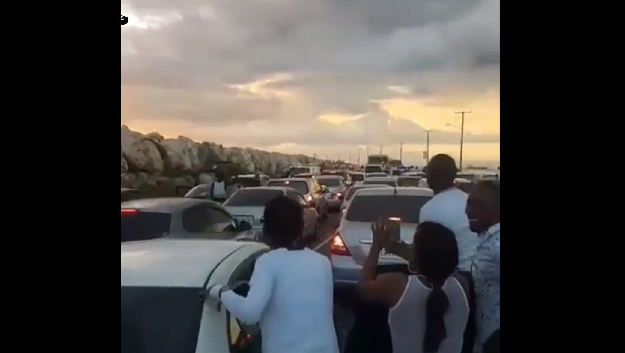 Screenshot of video circulating on social media shows a man carrying luggage towards the Norman Manley International Airport in Kingston amid a traffic pile-up along the Palisadoes strip on New Year's Day.