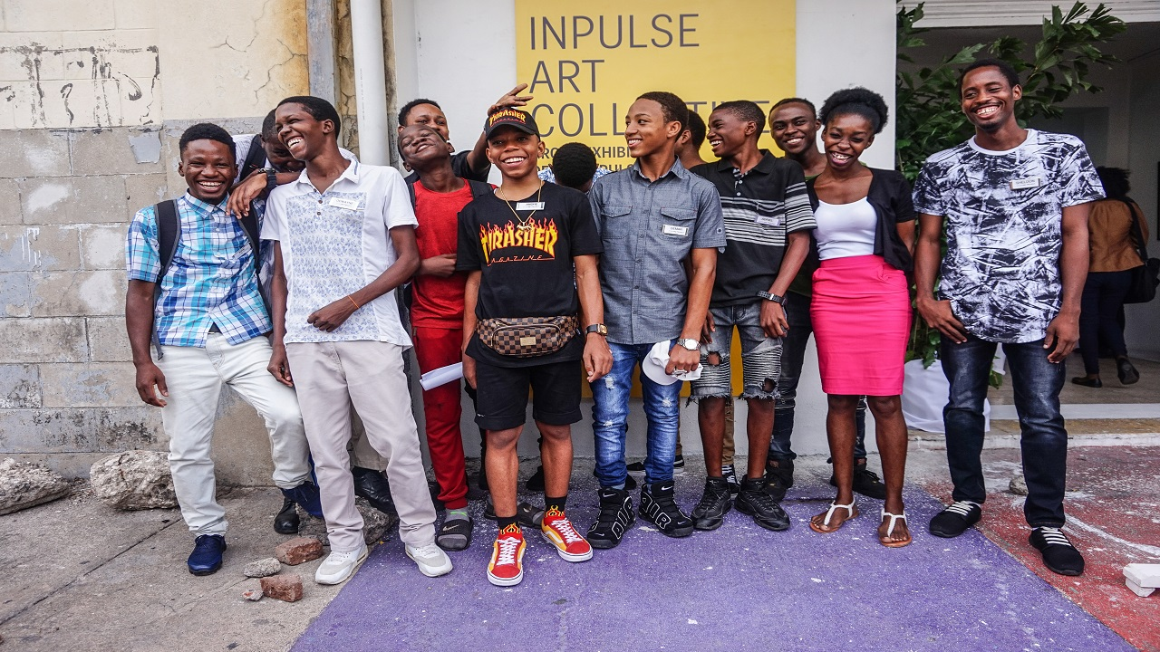 Project Manager of the InPulse Art Project Camille Chedda (center) poses with students of the initiative at the launch of an exhibition showcasing their work on Saturday, January 20 at Studio 174 in downtown Kingston.