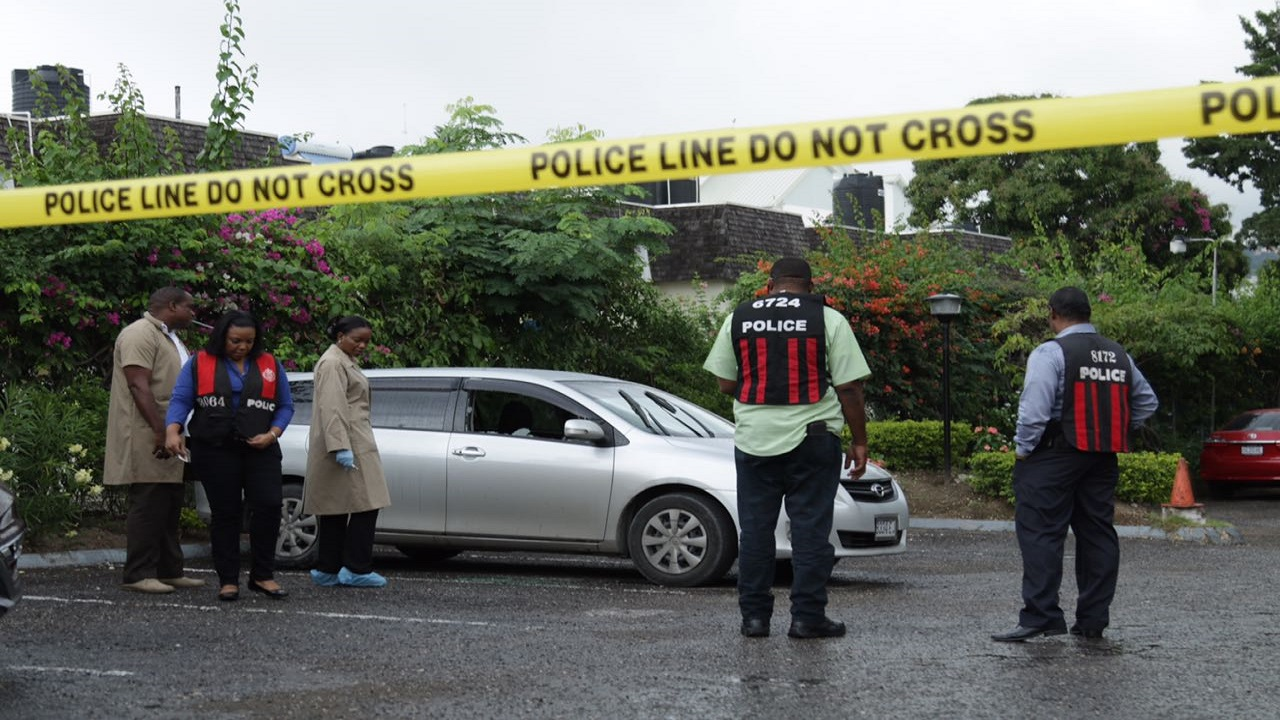 Police investigators around a motorcar in which two men were attacked and shot on the compound of financial entities Proven and Allied Insurance, on Belmont Road in New Kingston on Friday morning.