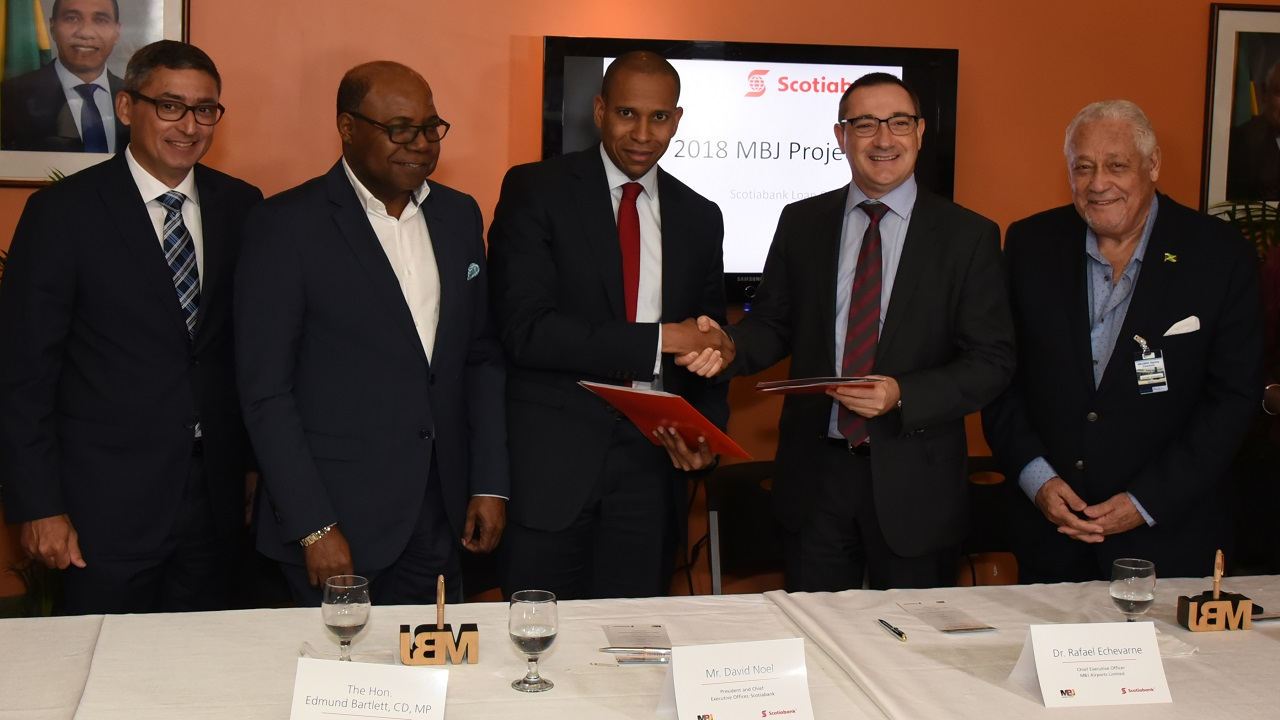 Scotia Group President and CEO, David Noel (3rd left) shakes the hand of Dr. Rafael Echevarne (2nd right), Chief Executive Officer MBJ Airports Limited, after the signing of a  loan agreement that will facilitate the expansion of the Sangster International Airport.  Sharing the moment from left are Craig Mair, SVP Corporate and Commercial, Edmund Bartlett, Minister of Tourism Mike Henry, Minister of Transport and Works.