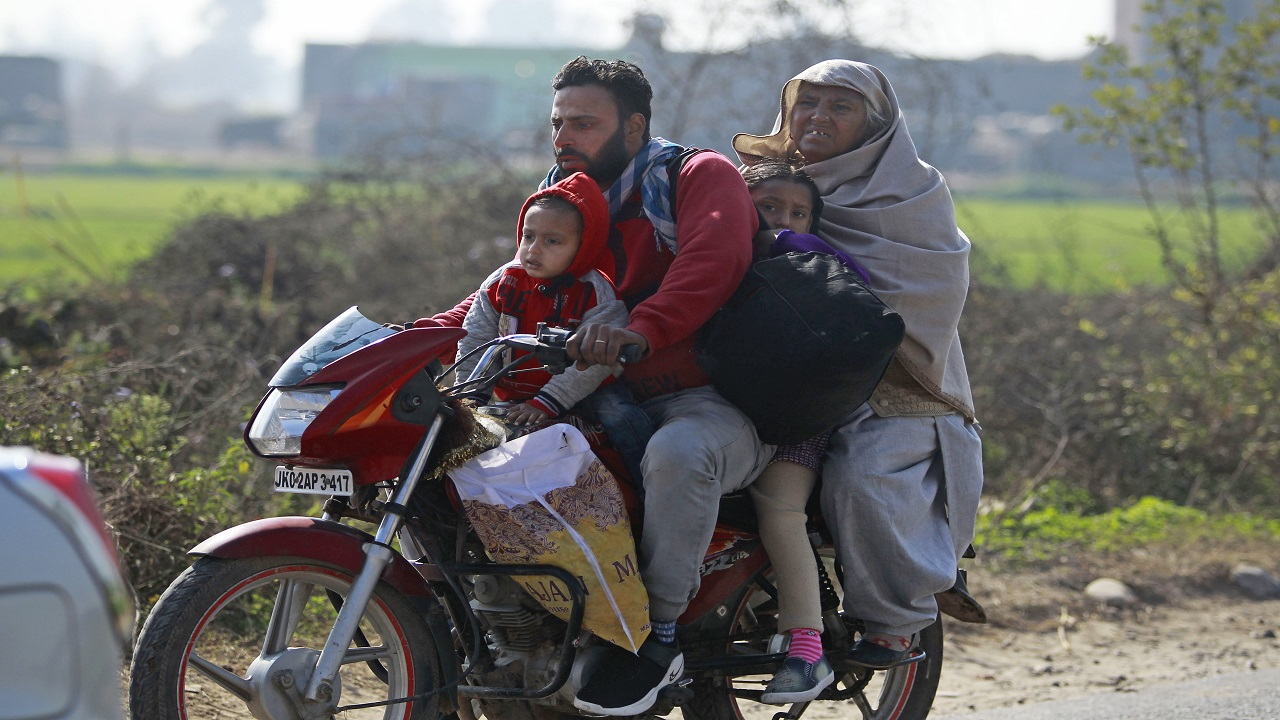 An Indian family rides a motorcycle as they move to a safer place following firing from the Pakistan side of the border in Ranbir Singh Pura district of Jammu and Kashmir, India, Saturday, Jan. 20, 2018.
