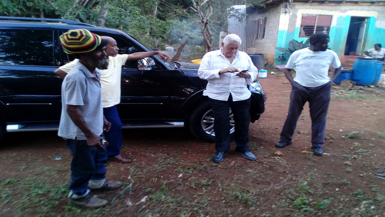 Central Clarendon Member of Parliament, Mike Henry (with phone in hand) on a visit to the home in Pleasant Valley where two young children died with foaming mouths last week.
