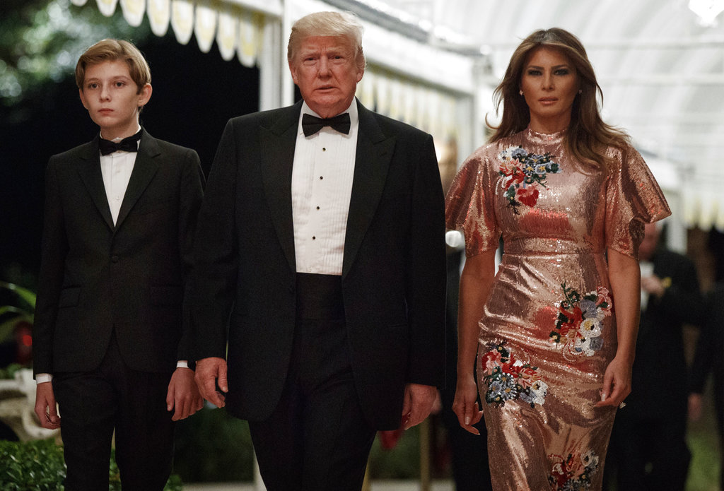 President Donald Trump arrives for a New Year's Eve gala at his Mar-a-Lago resort with first lady Melania Trump and their son Barron. (AP Photo/Evan Vucci)