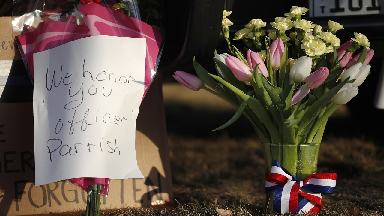 Tributes to a sheriff's deputy killed in a shootout are seen outside a Douglas County, Colo., Sheriffs Department substation Monday, Jan. 1, 2018, in Highlands Ranch, Colo.
