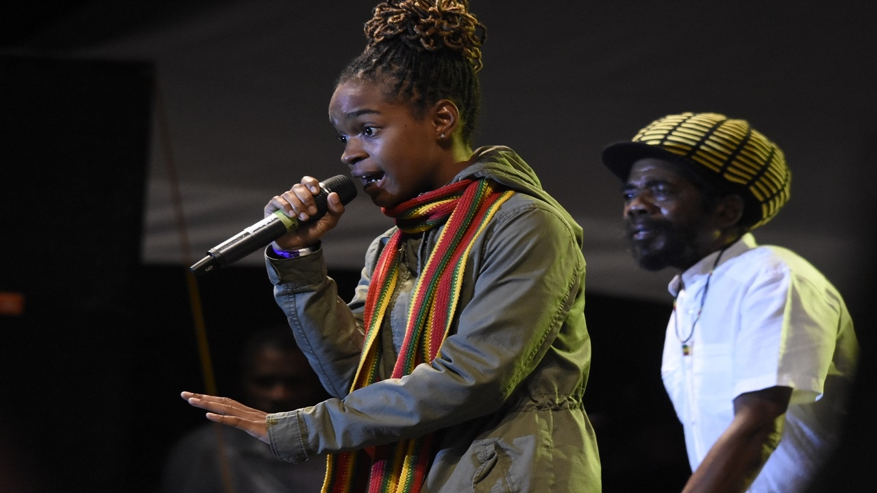 Veteran singer Cocoa Tea looks on from the background while his protege Koffee performs at Rebel Salute. (PHOTOS: Marlon Reid)
