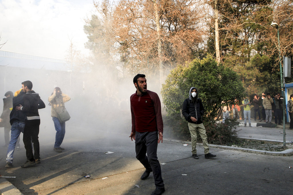 University students attend a protest inside Tehran University while a smoke grenade is thrown by anti-riot Iranian police. (AP Photo)