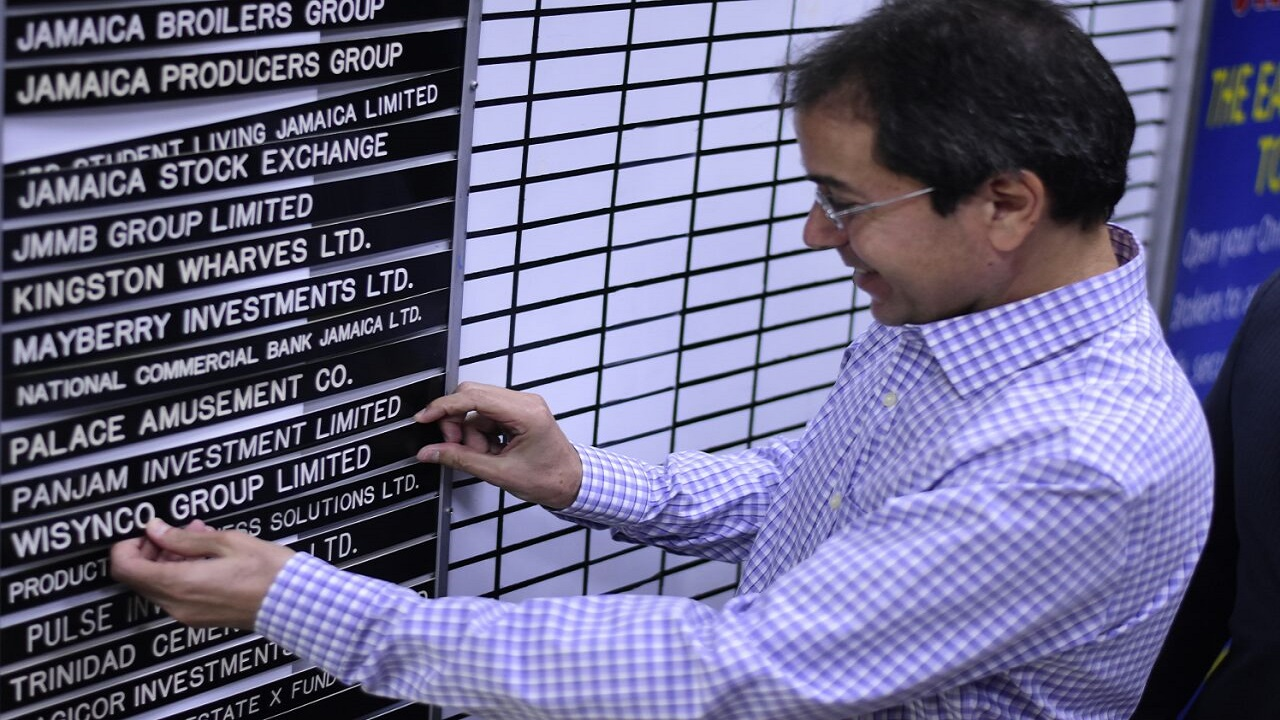 Wisynco CEO Andrew Mahfood places the company's name card on to the trading board at the Jamaica Stock Exchange listing ceremony on Thursday. (PHOTO: Marlon Reid)