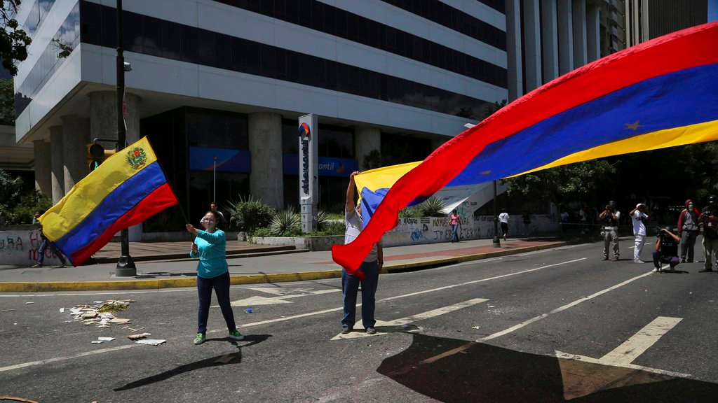 Anti-government demonstrators wave Venezuelan national flags during a protest against Venezuela's President Nicolas Maduro in Caracas, Venezuela, Tuesday, Aug. 8, 2017.
