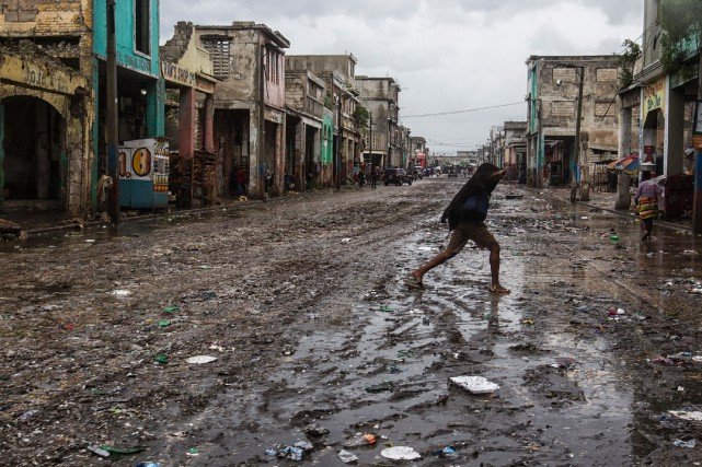 Une femme traverse une rue boueuse de Port-au-Prince. Photo: LOGAN ABASSI, ARCHIVES AGENCE FRANCE-PRESSE/UNICEF