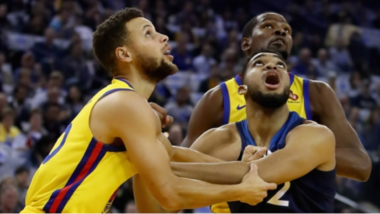 Stephen Curry (left), Karl-Anthony Towns and Kevin Durant fight for a rebound