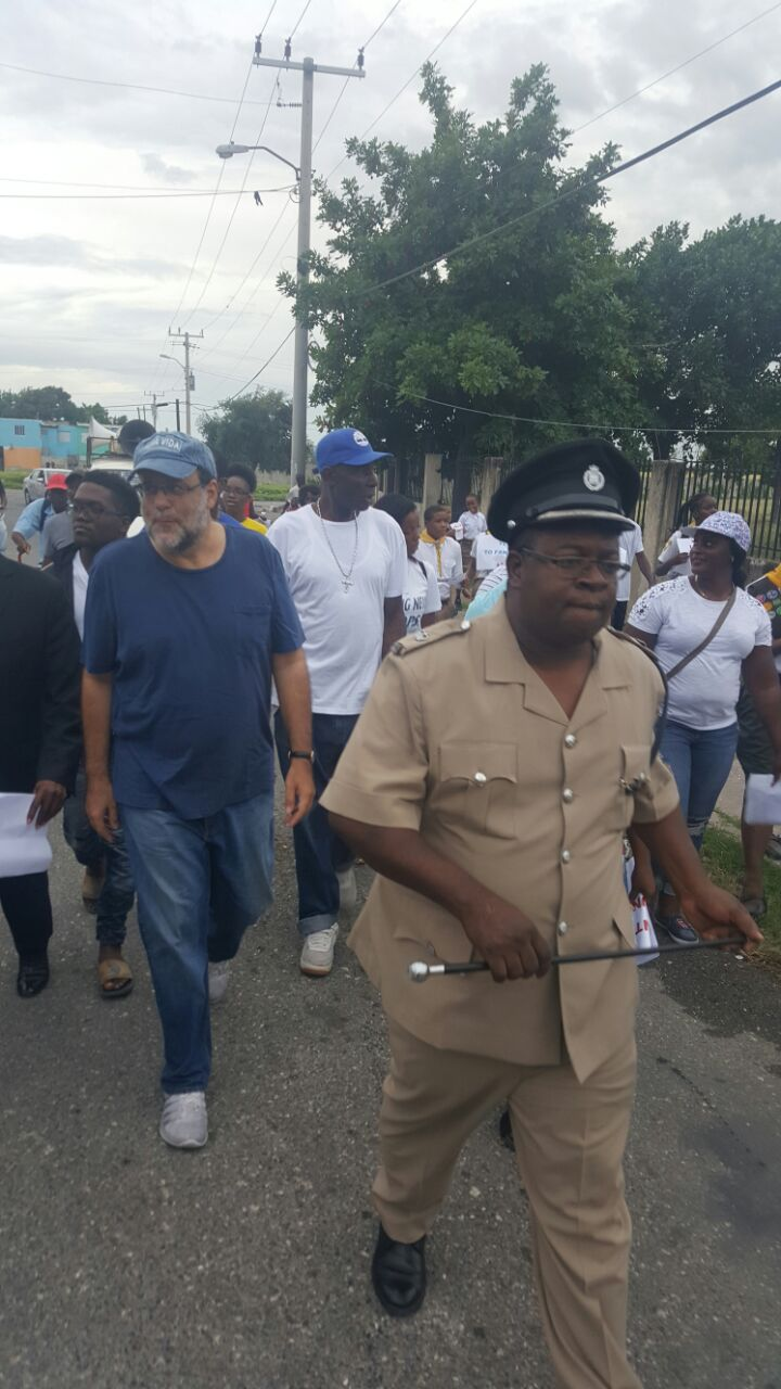Head of the Kingston Western Police Division, Superintendent Howard Chambers (foreground) and Member of Parliament (MP) for South St Andrew, Mark Golding (in blue), participate in a peace march in the police division on Saturday.