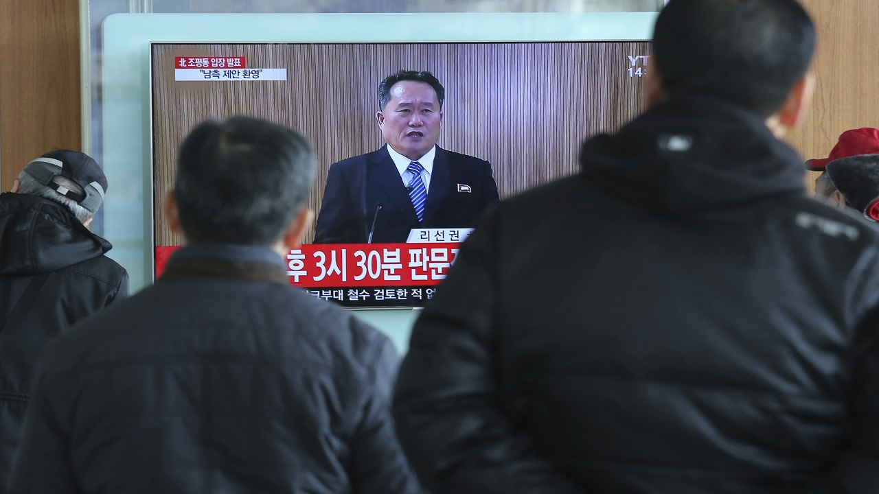 Travelers watch a public TV screen showing a North Korean newscaster reading a statement at the Seoul Railway Station in Seoul, South Korea, Wednesday, Jan. 3, 2018.