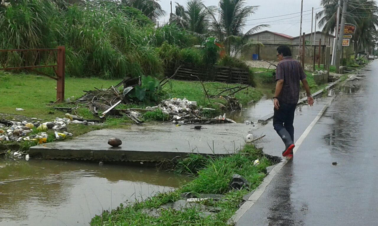 Minister Kazim Hosein surveys illegal dumping in the Caroni region following floods.
