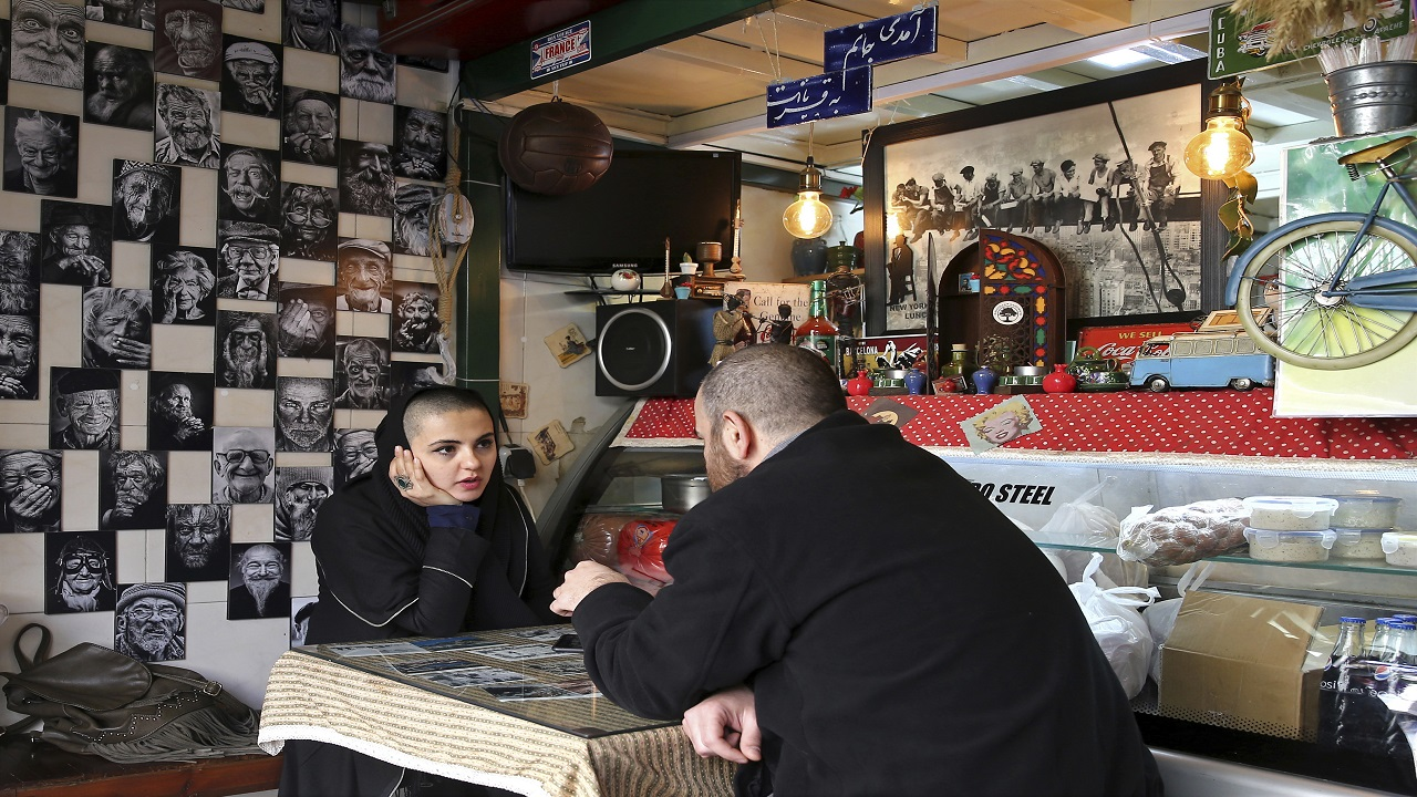 Two young Iranians sit in a fast food restaurant in downtown Tehran, Iran, Wednesday, Jan. 3, 2018. Tens of thousands of Iranians took part in pro-government demonstrations in several cities across the country on Wednesday, Iranian state media reported, a move apparently seeking to calm nerves after a week of protests and unrest that have killed at least 21 people.