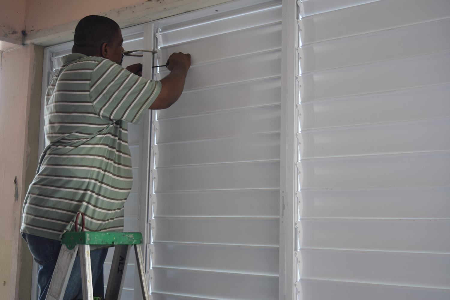 A worker installs a new window in a classroom at the St Joseph Secondary School as the December Vacation Repair Programme gets underway.