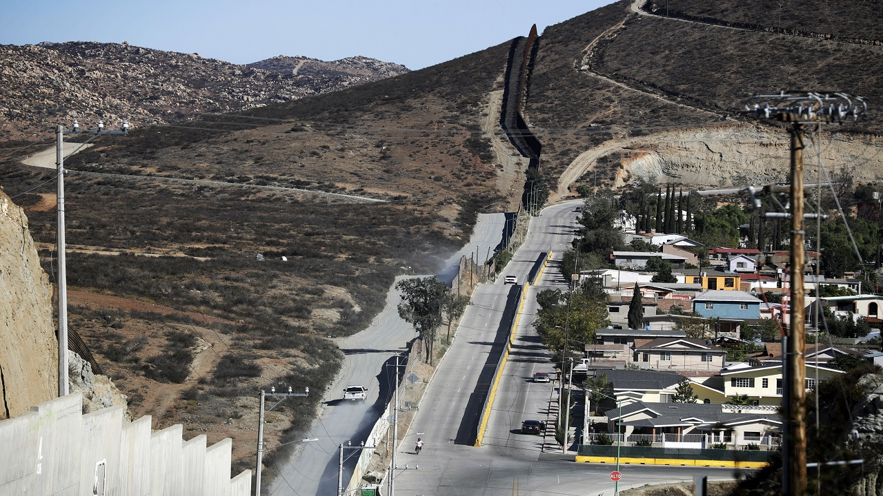 In this Nov. 9, 2016 file photo, a Border Patrol vehicle drives by the border fence in Tecate, Calif., left, along the metal barrier that lines the border, seen from Tecate, Mexico. The Trump administration has proposed spending $18 billion over 10 years to significantly extend the border wall with Mexico.