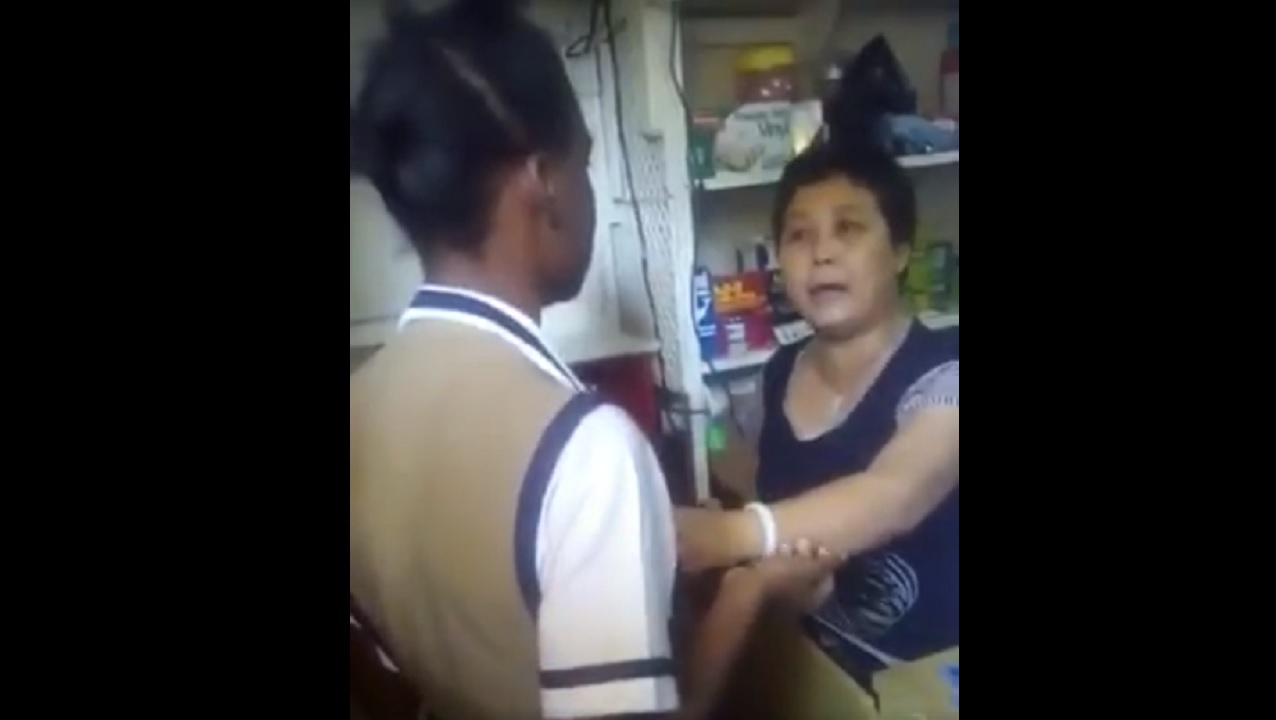 Screenshot shows a shop operator grabbing a child inside her business establishment.