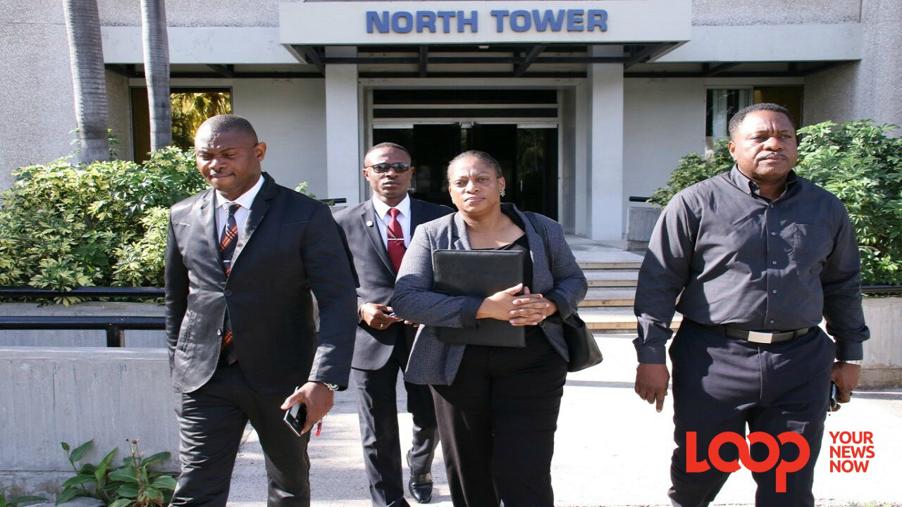 Chairman of the Police Officer's Association Catherine Lord (centre) exists the Ministry of National Security on Oxford Road. She is accompanied by Assistant Superintendent St George Jackson (left), Superintendent David Whyte (right) and DSP Christopher Phillips (background).