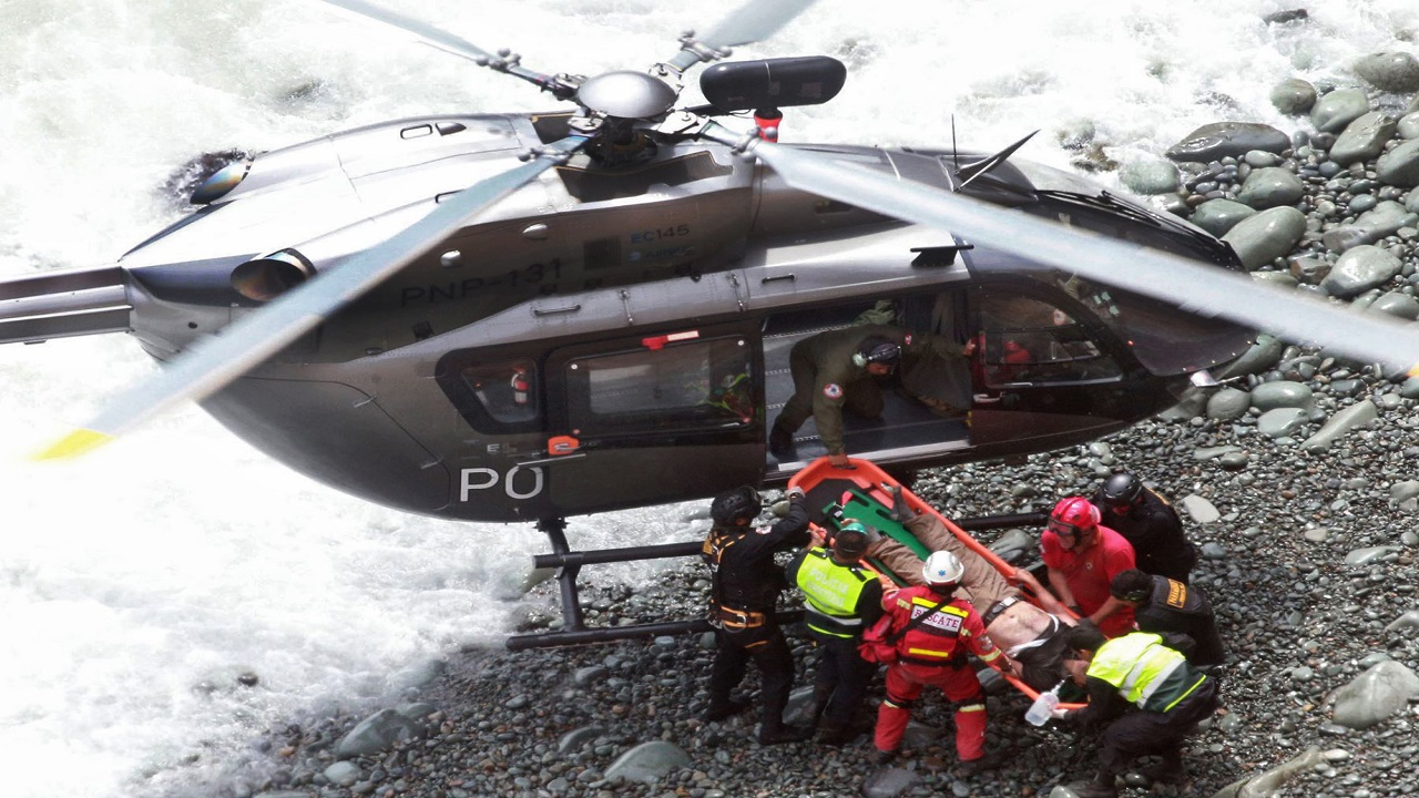 In this photo provided by the government news agency Andina, rescue workers load an injured man on a stretcher after he was retrieved from a bus that fell off a cliff after it was hit by a tractor-trailer rig, in Pasamayo, Peru, Tuesday, Jan. 2, 2018. A Peruvian police official says at least 30 people died, and that there were more than 50 people on the bus.