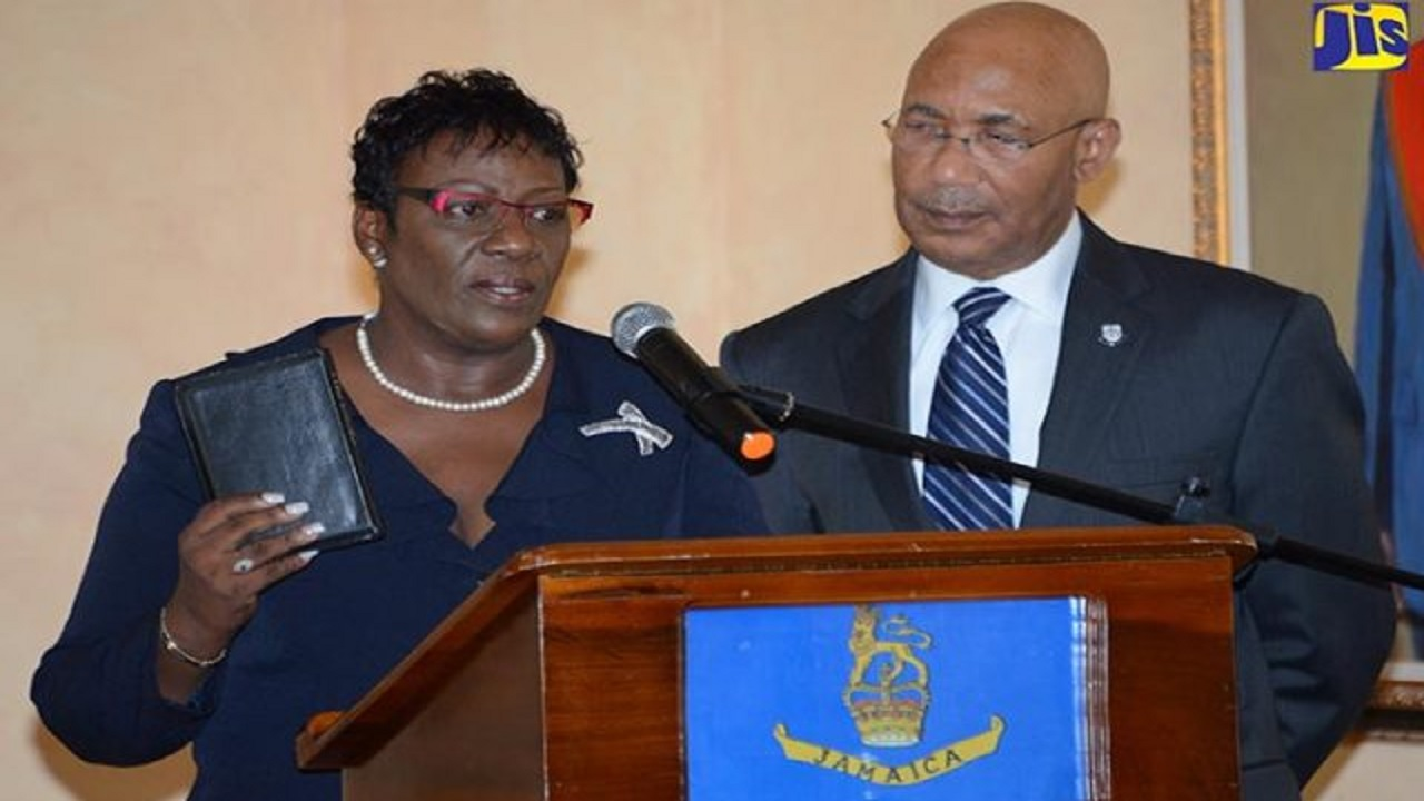Judith Pusey takes the Oath of Allegiance and the Judicial Oath as the country's first Chief Judge of the Parish Courts, during a swearing-in ceremony at King's House in September 2016. Governor General Sir Patrick Allen looks on. (PHOTO: JIS)
