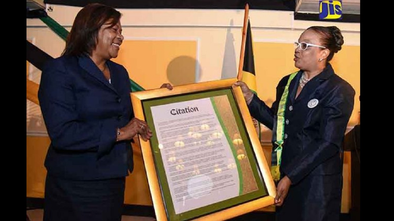 Outgoing Chief Justice, Zaila McCalla (left), accepts a citation from Puisne Judge and Assistant Secretary of the Jamaica Association of Women Judges (JAWJ), Justice Carol Edwards. Occasion was a ceremony in Justice McCalla's honor at the Terra Nova Hotel in Kingston on January 26.