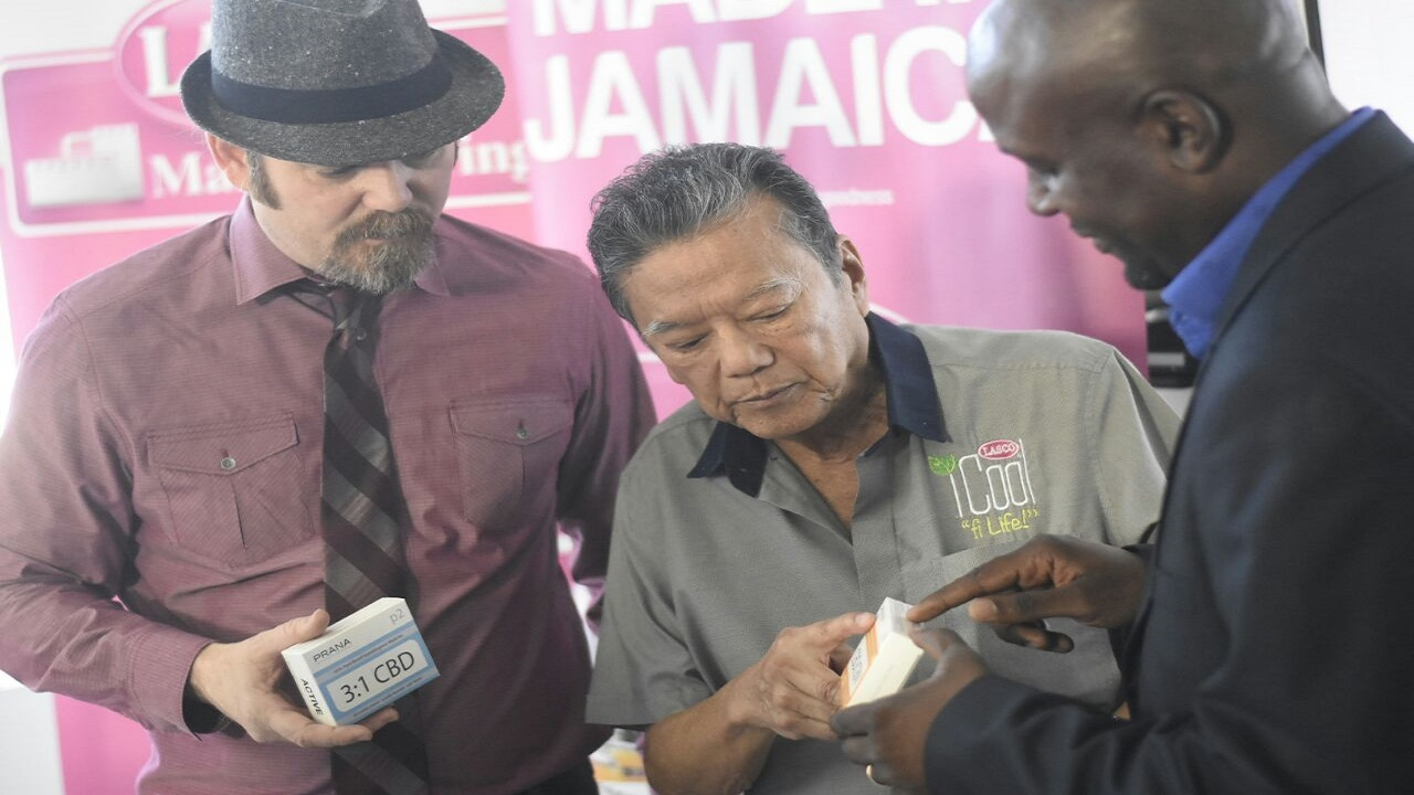 Lasco chairman Lascelles Chin (centre) examines a product with Kenyama Brown (right), of Cannabinoid Research and Development Company, while CEO of UCANN, Earnie Blackmon, looks on. (PHOTO: Marlon Reid)