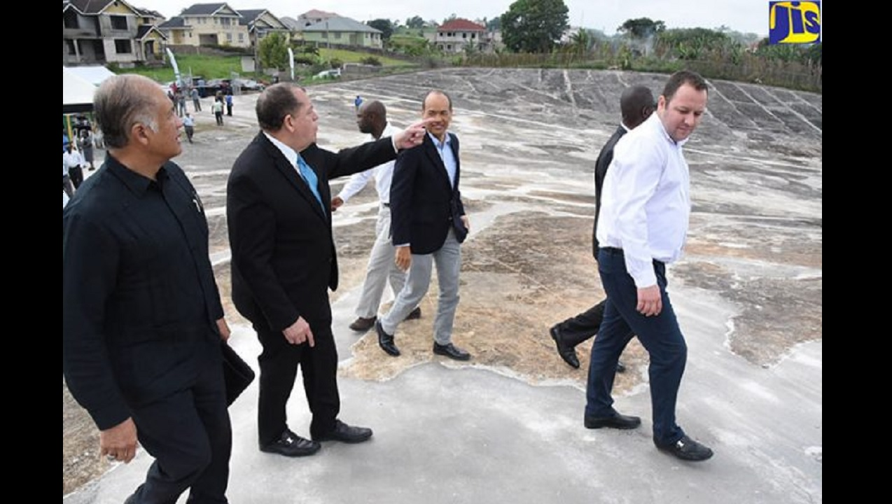 Finance Minister and MP for North East Manchester, Audley Shaw (second left), points out something of interest to Chairman of Caribbean Cement Company, Dr Parris Lyew-Ayee (left); and Chairman of the Southern Regional Health Authority, Wayne Chen (third left), as they walk along the freshly repaved water-harvesting facility at Percy Junor Hospital in Spaldings, Manchester.