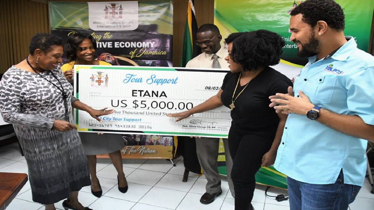 Reggae singer Etana (second right) points to the symbolic US$5,000 cheque while Entertainment Minister Olivia Grange (left) and others look on at a ceremony last week.