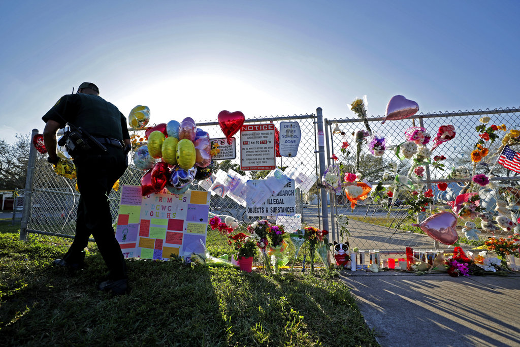 A Broward County Sheriff's Office deputy removes police tape from a makeshift memorial at Marjory Stoneman Douglas High School in Parkland, Florida. (John McCall/South Florida Sun-Sentinel via AP)