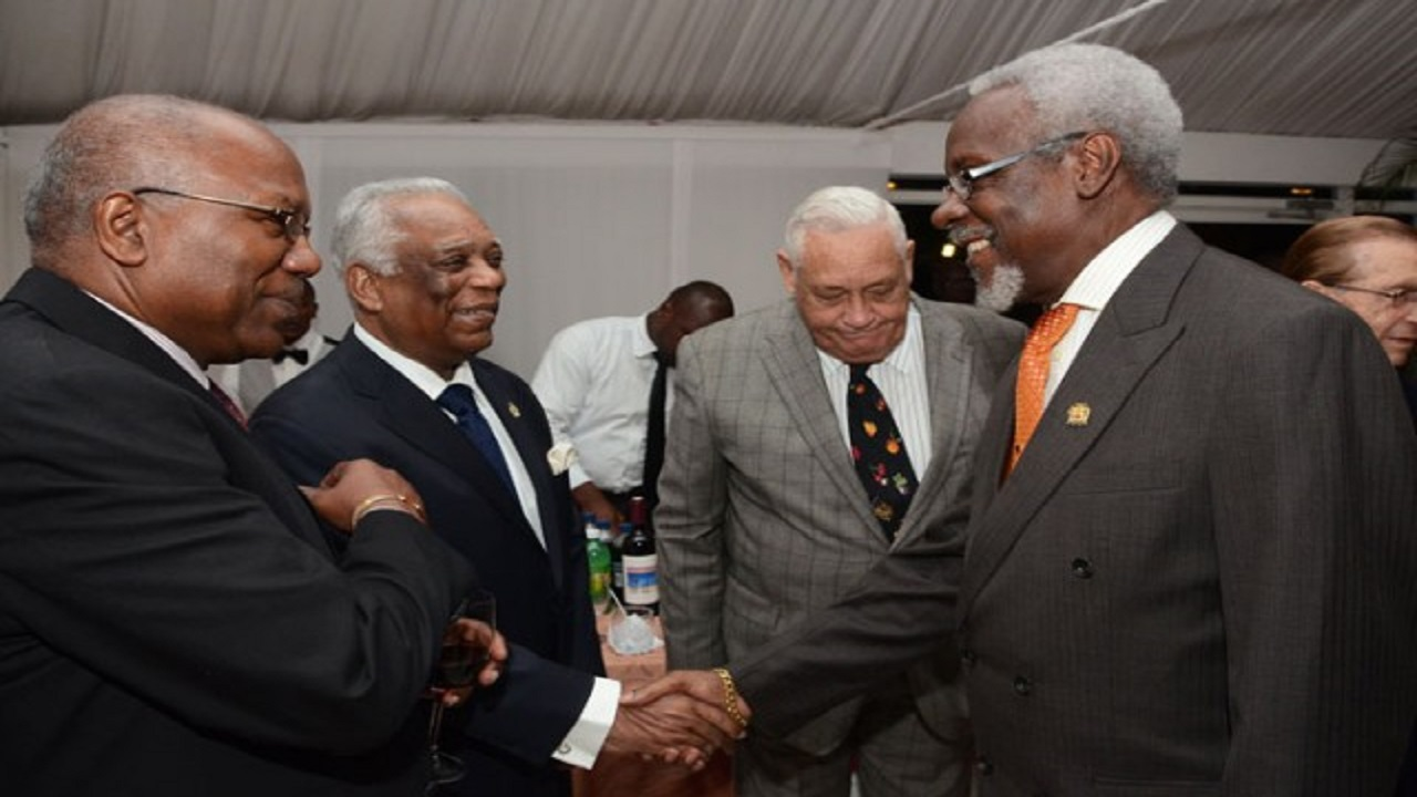 Former Prime Minister, PJ Patterson (right), greets retired Chairman, President and CEOof the Port Authority of Jamaica, Noel Hylton (second left), on his arrival at the Terra Nova Hotel in Kingston on October 31, 2013 for a dinner hosted in Hylton's honour. Others from left are: then Minister with responsibility for Housing, Dr Morais Guy; Member of Parliament for Central Clarendon, Mike Henry; and former Prime Minister, Edward Seaga (in background).