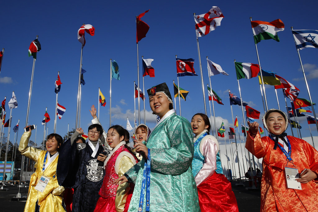 A group of volunteers wearing handbook, Korean traditional dress, greet athletes entering the Olympic Village as flags including North Korea's, fly prior to the 2018 Winter Olympics in Gangneung, South Korea. (AP Photo/Jae C. Hong)