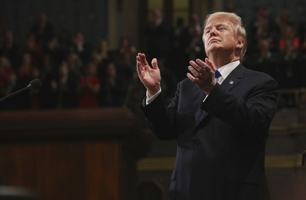 President Donald Trump claps at his first State of the Union address in the House chamber of the U.S. Capitol to a joint session of Congress in Washington. (Win McNamee/Pool via AP)