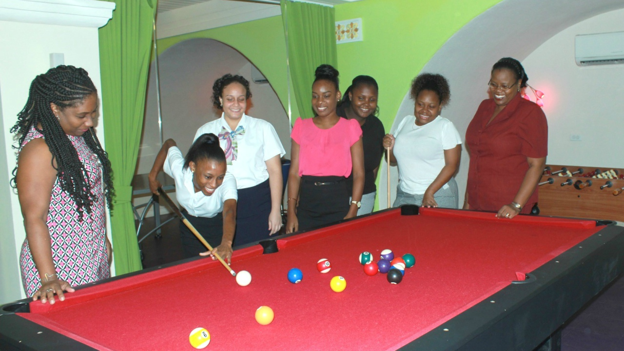 Students of the Barbados Community College's Hospitality Institute taking time to enjoy a friendly game of pool on the last day of their internship programme at Elegant Hotels while Tutor Lynette Francis-Thornhill (right) and Elegant's Cindy Miller (left) look on.
