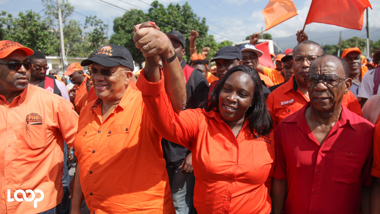 PNP candidate for North West St Andrew, Keisha Hayle arrives hand in hand with Opposition Leader Dr Peter Phillips on Nomination Day, while PNP general secretary Julian Robinson (left) and Hayles' campaign manager Paul Buchanan look on. (PHOTOS: Shawn Barnes)