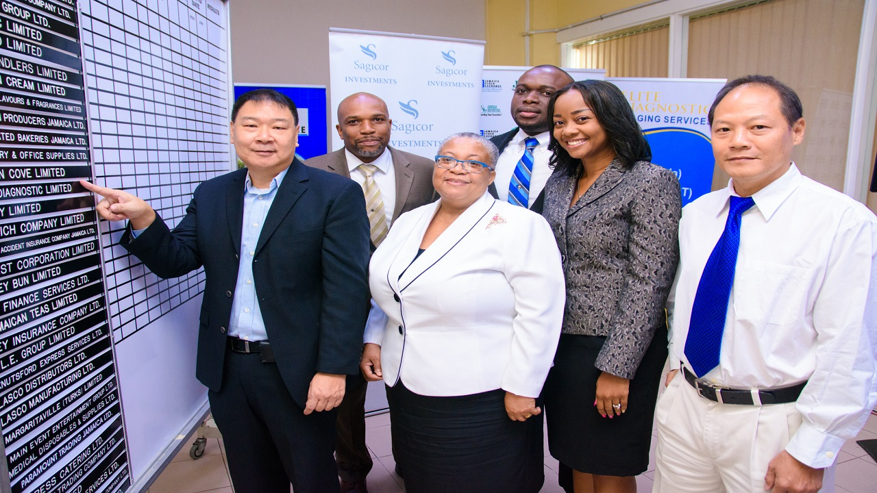 Warren Chung (left), CEO at Elite Diagnostic Limited proudly points to his company's name listed on the Junior Market of the Jamaica Stock Exchange. Also photographed are, Herbert Hall, Assistant Vice President, Investment Banking; NCB Capital Markets, Marlene Street Forrest, Managing Director, JSE; Denton Dewar, Manager,  Origination and Structuring at NCBCM; Mischa McLeod-Hines, Manager, Capital Markets, Sagicor Investments Limited and Neil Fong COO and Medical Director, Elite Diagnostic Limited.