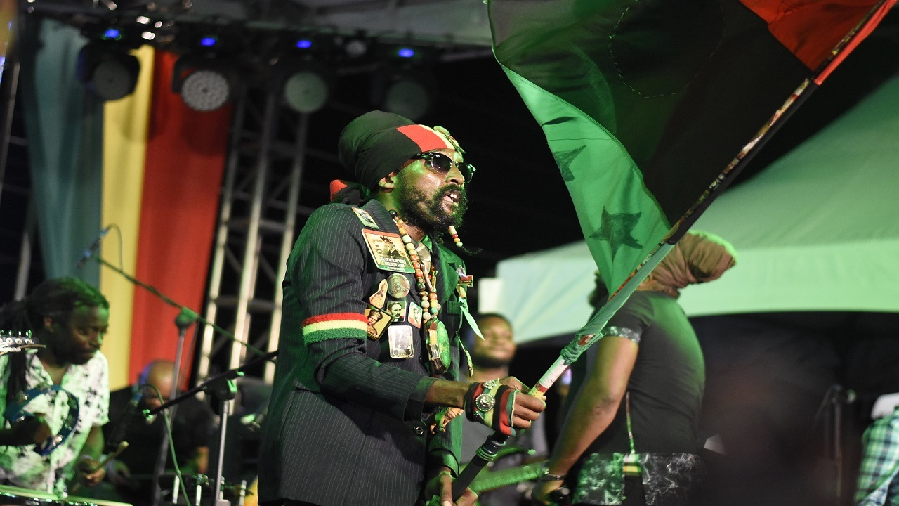 A Rastafarian man waves a flag during a jam session at the Bob Marley Museum in Kingston on Tuesday. The event was part of activities in celebration of the 73rd birthday anniversary of the reggae legend. (PHOTOS: Marlon Reid)