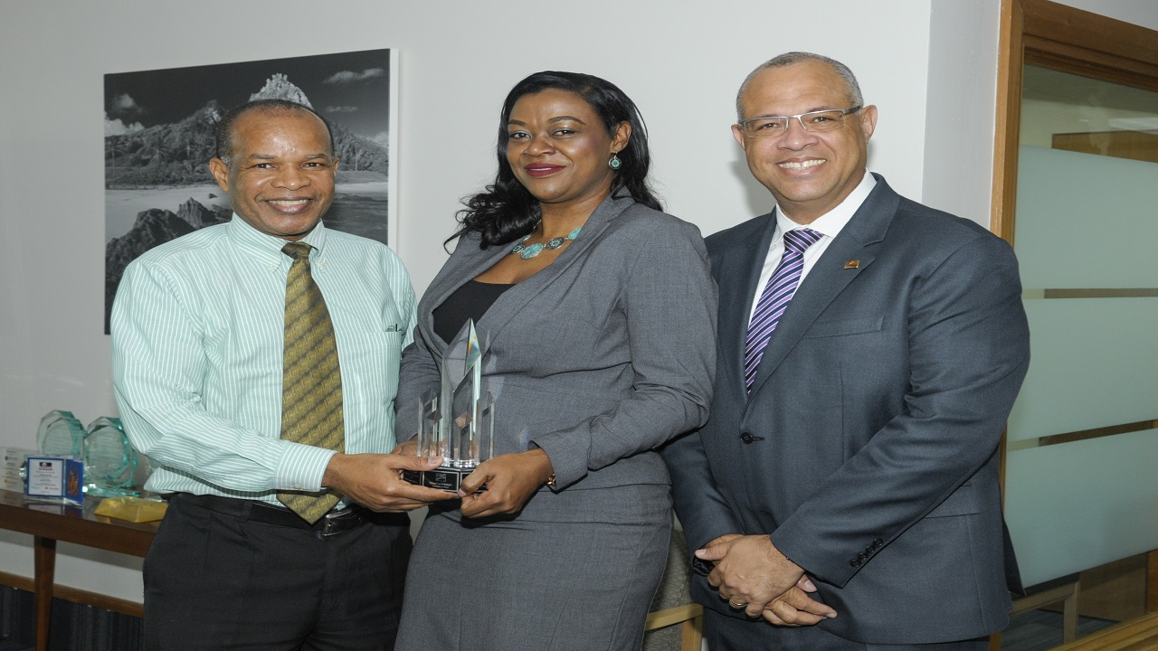 "CEO of CIBC FirstCaribbean International Bank, Gary Brown (2nd right) presents the bank's ""Branch of the Year Award 2017"" to Marion Wilson, Branch Manager  Sharing the moment are Owen Francis (left), Director Retail Banking Channels and Mark St. Hill, Managing Director, Retail Business & International Banking."