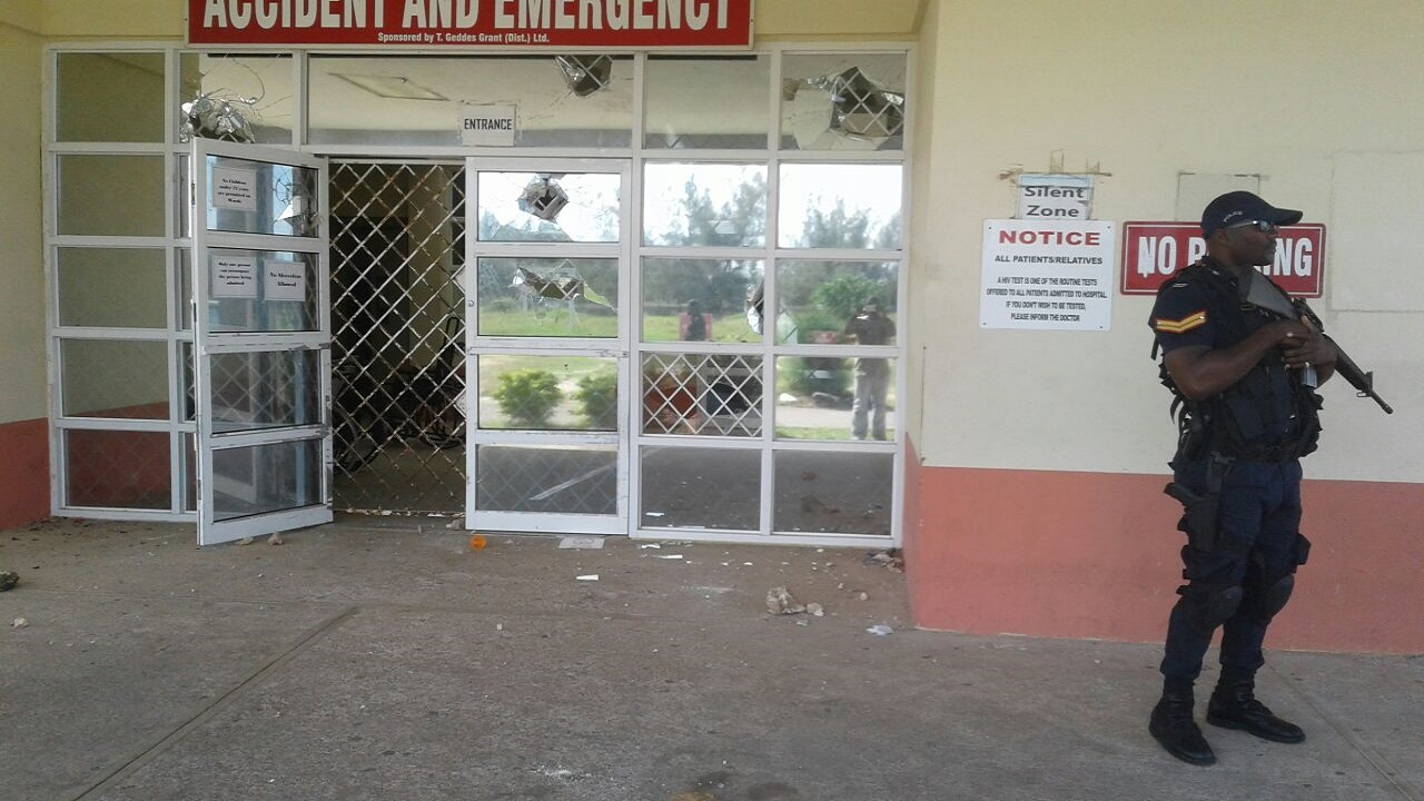 A heavily-armed policeman on guard outside the Accident and Emergency Ward at the Falmouth Hospital in Trelawny, which was stoned by visitors at the facility on Sunday morning after the death of a patient who was involved in a motor vehicle collision. Shattered glass panes at the entrance to the building are evident in the background.