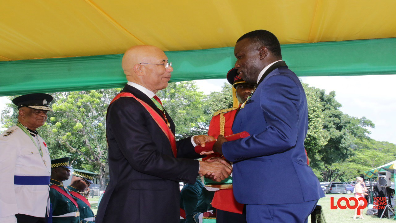 Reggae Boyz coach Theodore Whitmore collects his national award from Governor General Sir Patrick Allen. (Photo: Llewellyn Wynter)