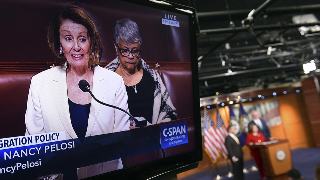 (Image: AP: Nancy Pelosi is shown on television as she speaks from the House floor in Washington on 7 February 2018)
