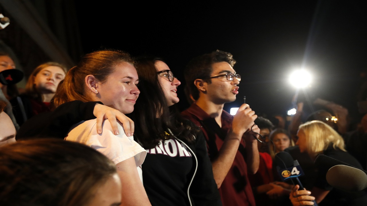 This Feb. 20, 2018 file photo shows Diego Pfeiffer, a student survivor from Marjory Stoneman Douglas High School, speaking to a crowd of supporters and media, while fellow survivors Sophie Whitney, left, and Sarah Chadwick embrace in Tallahassee, Fla. The latest mass shooting at the Florida high school has some pondering the improbable: Could this one actually bring some measure of change?