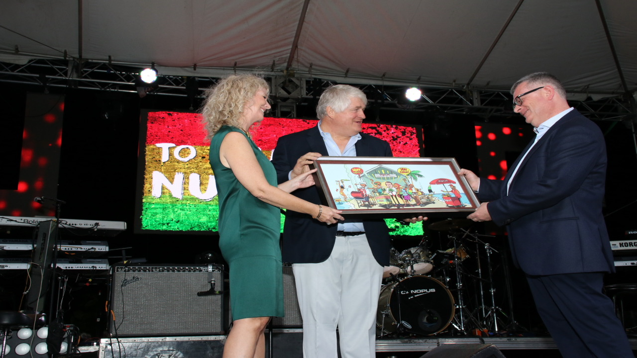 Outgoing Digicel Group CEO, Colm Delves (right) receives a framed Clovis cartoon from company founder and chairman Denis O'Brien and CEO of Caribbean and Central America, Vanessa Slowey. (PHOTO: Llewellyn Wynter)