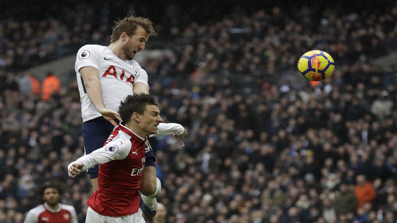 Tottenham Hotspur's Harry Kane, top, leaps above Arsenal's Laurent Koscielny to score in their English Premier League football match  at Wembley stadium in London, Saturday, Feb. 10, 2018.