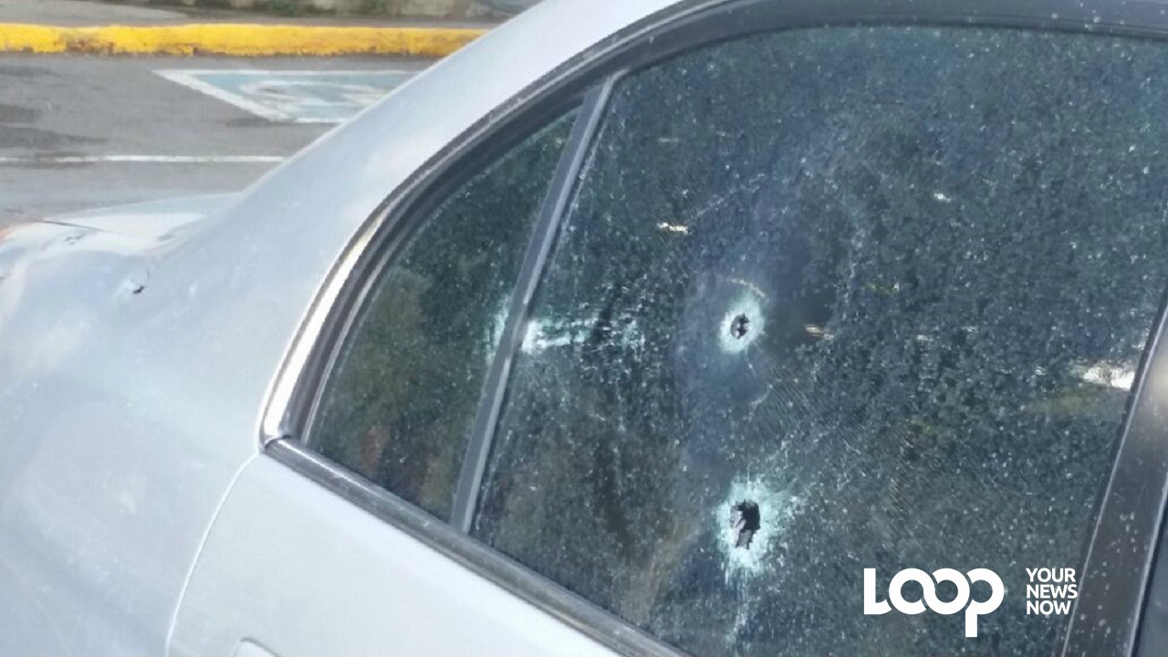The damaged window of the car that was being driven by a businessman when he was attacked by gunmen in rush hour traffic in St Andrew on Friday morning.