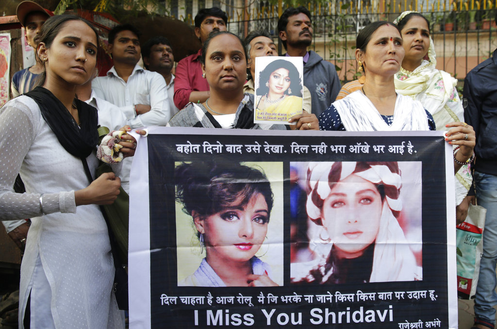 Fans of Bollywood actress Sridevi hold posters as they wait outside her residence to pay their last respects in Mumbai, India. (AP Photo/Rafiq Maqbool)