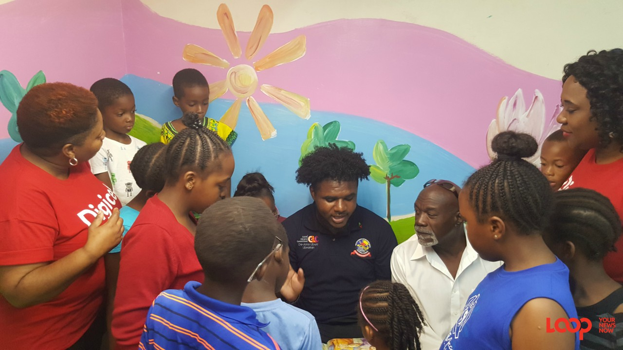 Digicel staff and young readers listening to the UWI library student read aloud.
