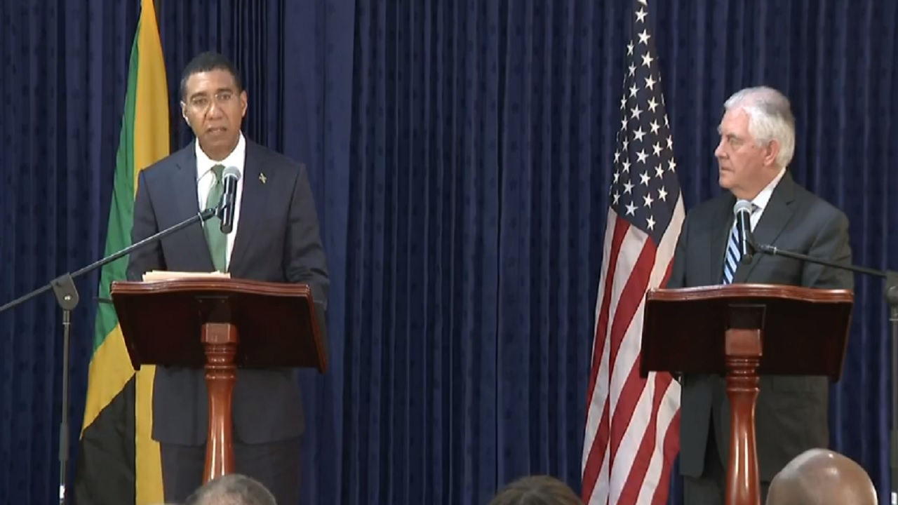 Jamaica's Prime Minister Andrew Holness (right) addresses journalists while 