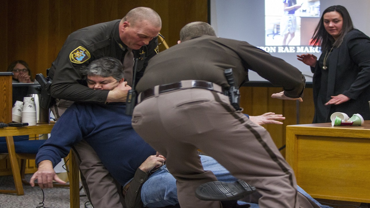 Eaton County Sheriff's deputies restrain Randall Margraves, father of three victims of Larry Nassar, Friday, Feb. 2, 2018, in Eaton County Circuit Court in Charlotte, Mich.