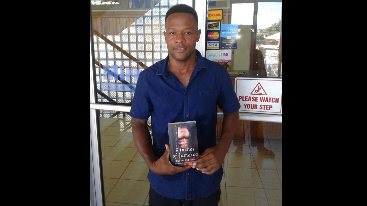 Albert 'Richard' Robinson shows off his new book, 'Nine Inches of Jamaica'.