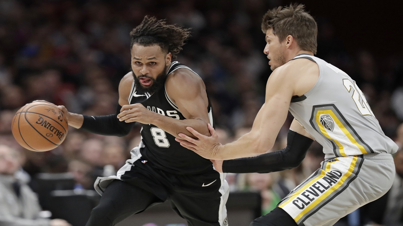 San Antonio Spurs' Patty Mills (8) is fouled by Cleveland Cavaliers' Kyle Korver (26) in the first half of an NBA basketball game, Sunday, in Cleveland. (AP Photo/Tony Dejak)